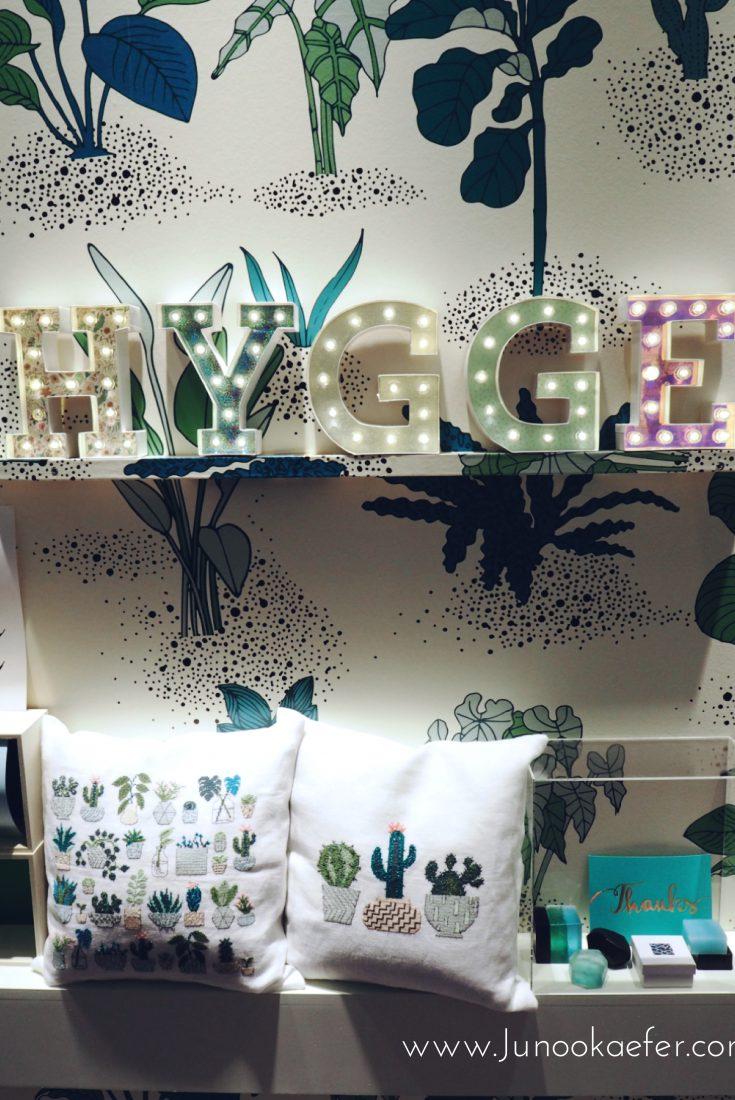 Bild der Kreativmesse mit Leuchtbuchstaben die Hegge schreiben. Es ist alles Grün mit Pflanzenbildern als Hintergrund und Kissen auf denen Kakteen gestickt sind