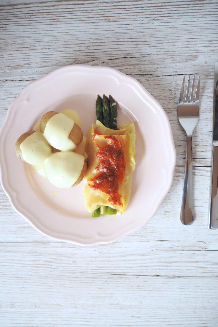 Grüner Spargel eingewickelt in Lasagneblatt und Schinken mit gekochten Kartoffeln und Sauce Hollandaise auf einem rosa Teller