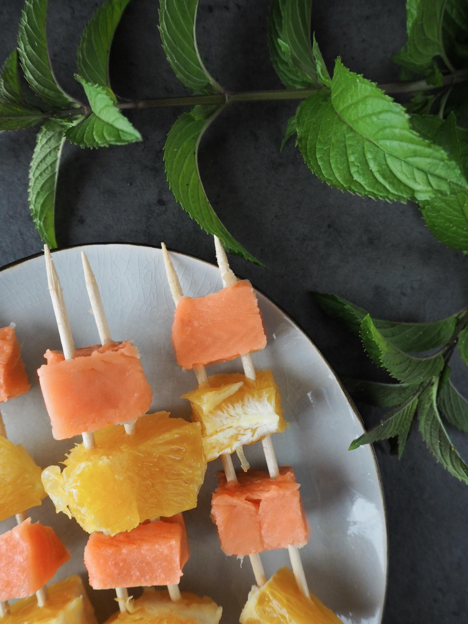 Orangen-Lachsspieße roh auf dunklem Untergrund, oben mit Minze dekoriert