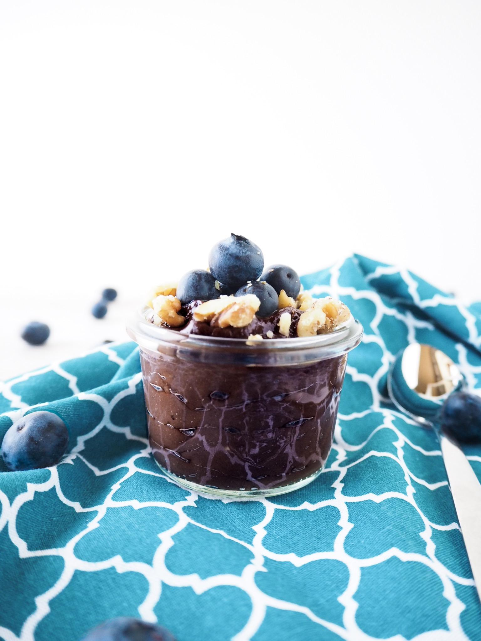 veganer Schokopudding mit türkisem Küchentuch dekoriert mit Blaubeeren und Walnüssen