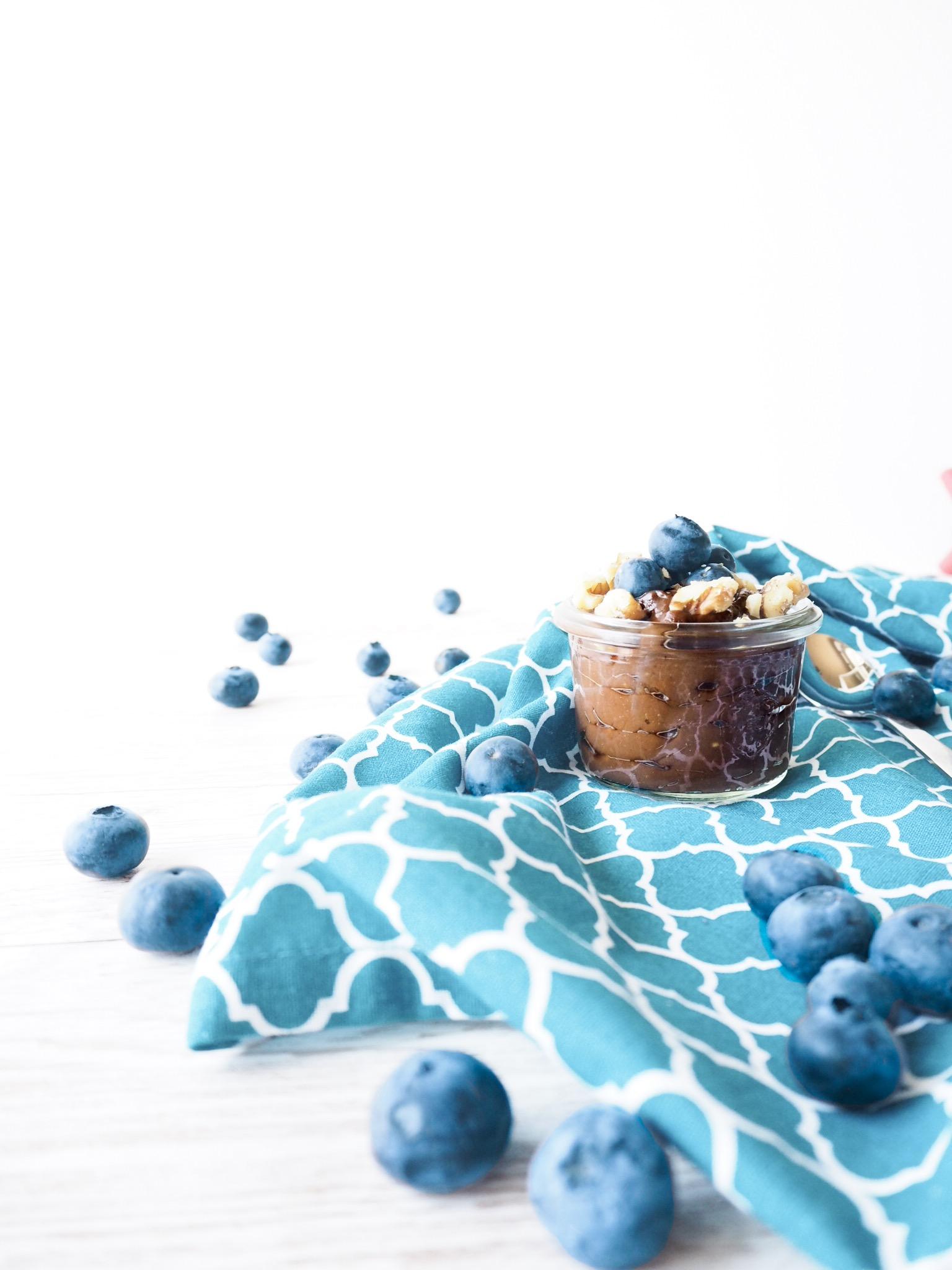 Veganer Schokopudding auf türkisem Küchentuch mit Blaubeeren als Deko drum herum