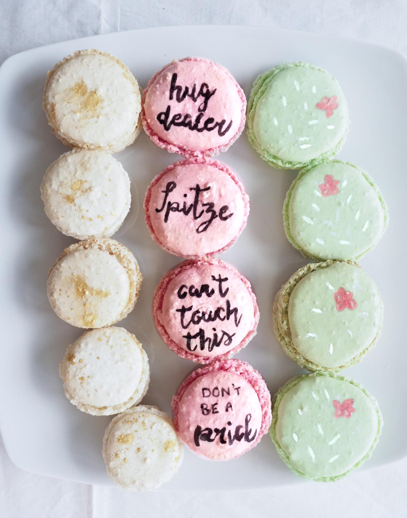Macarons in Rosa, Grün und Sandfarben dazu beschriftet mit Spitze, Can´t touch this, don´t be a prick und hug dealer